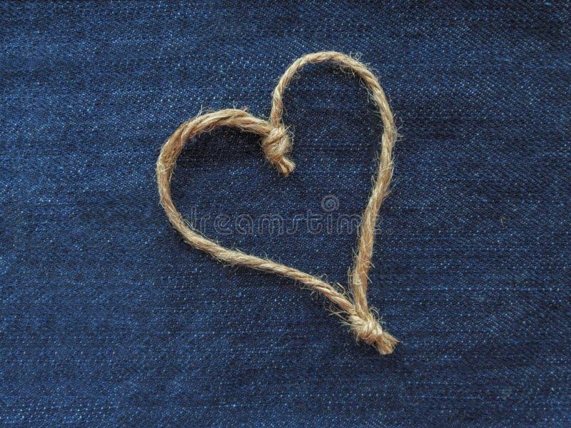 麻线的标志心脏在牛仔布的 图库摄影