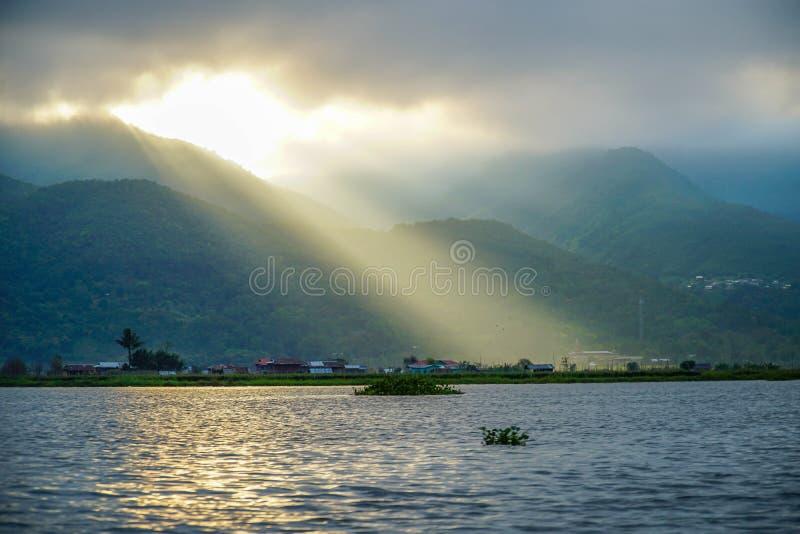 黄昏光芒 发光通过云彩的太阳在缅甸的缅甸Inle湖 库存照片