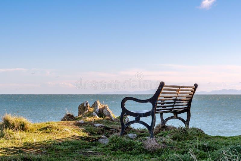 黄昏前俯视海的一条空的长凳 免版税库存照片