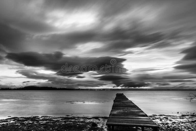 黄昏时分,在一片充满戏剧性、情绪化的天空下,能看到湖上的一座码头 库存照片