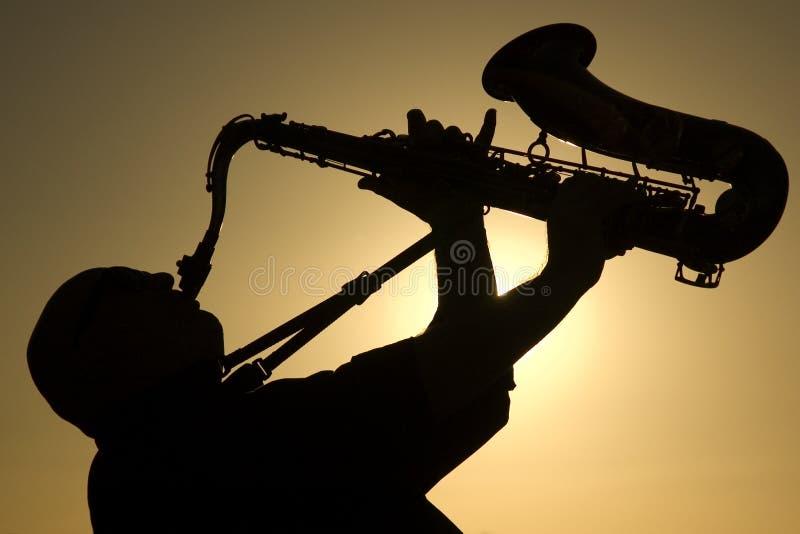 黄昏萨克斯管吹奏者 免版税库存照片