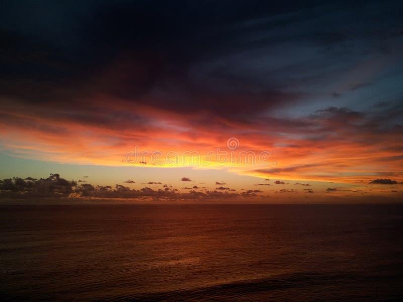 黄昏-海上显示温暖的黄色焕发和蓝蓝色彩天空的太阳设置 免版税库存图片