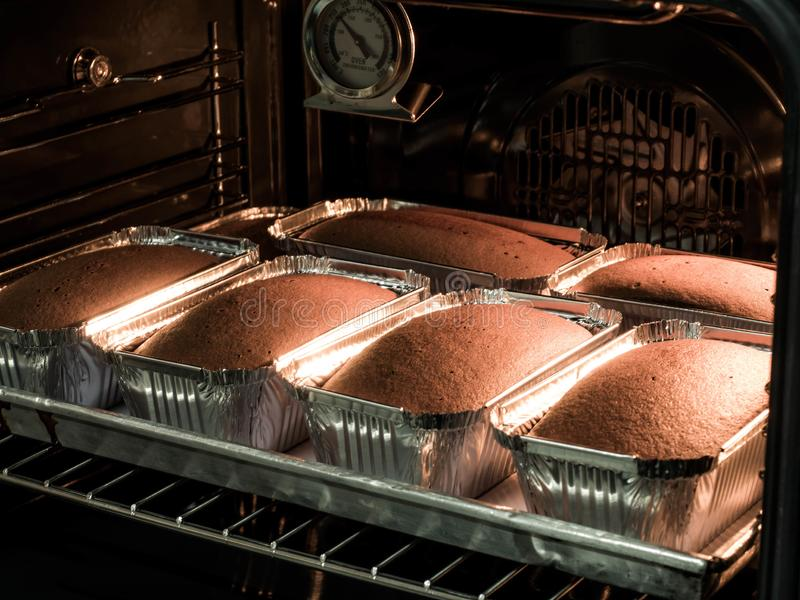 黄油蛋糕在烤箱被做 在面包店的生产烤箱 烘烤面包 面包制造  免版税库存图片