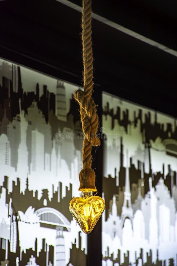 黄灯电灯泡心形垂悬与绳索 免版税库存照片