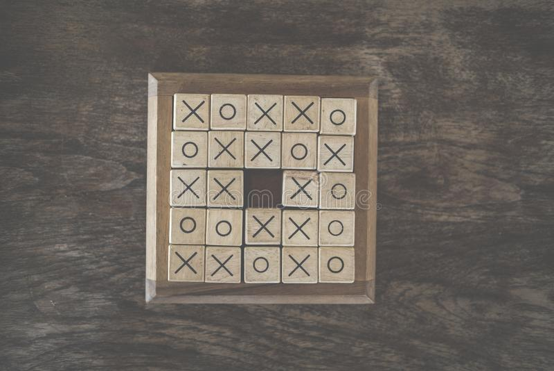 黄牛木刻做的井字游戏比赛在木桌 Educatio 免版税图库摄影
