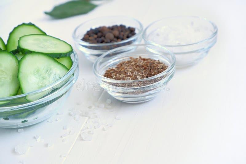 黄瓜在picklingfermenting-莳萝种子的,胡椒,在一张白色木桌上的盐一个玻璃碗香料切了 库存图片
