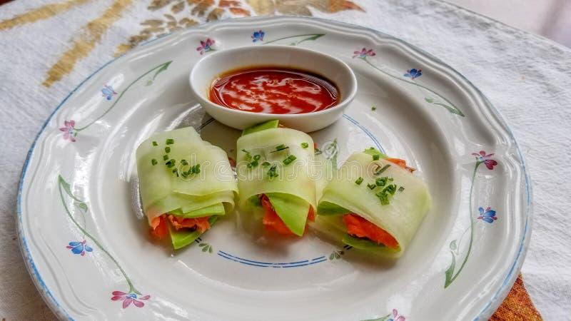 黄瓜套做了用在鲕梨附近被包裹的非常稀薄地切的黄瓜,并且冷的熏制鲑鱼熏鲑鱼,冠上了用新鲜的香葱, 免版税图库摄影