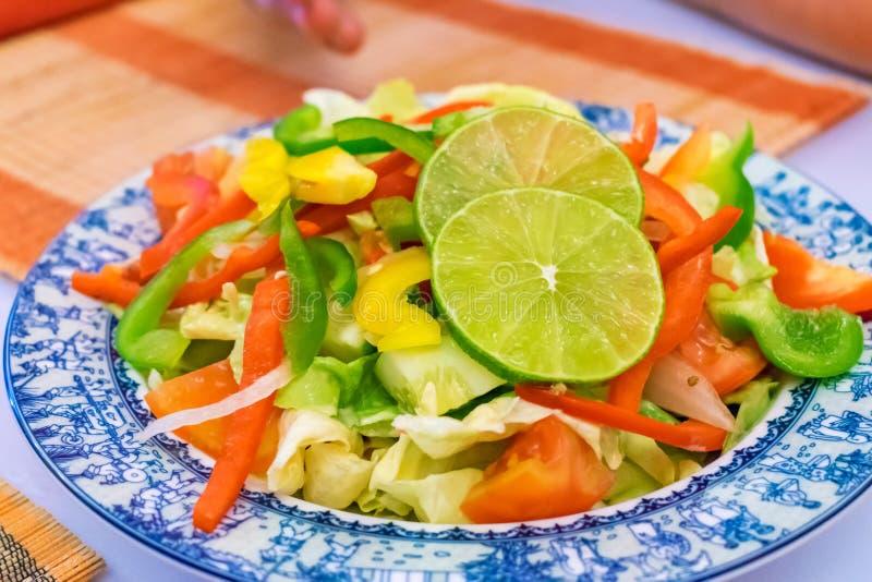 黄瓜沙拉用蕃茄和切片在板材的石灰 免版税库存照片