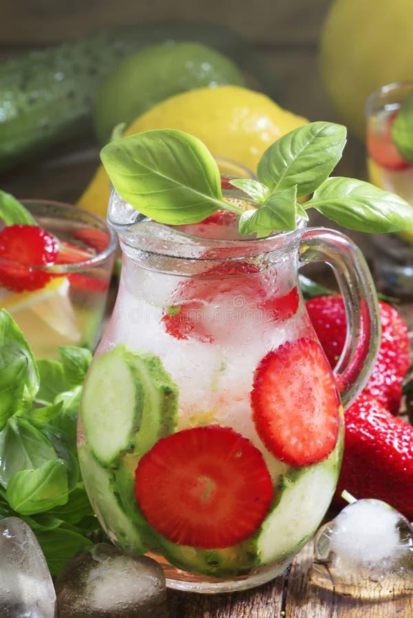 黄瓜草莓与冰的蓬蒿柠檬水在水罐,葡萄酒木桌,选择聚焦 免版税图库摄影