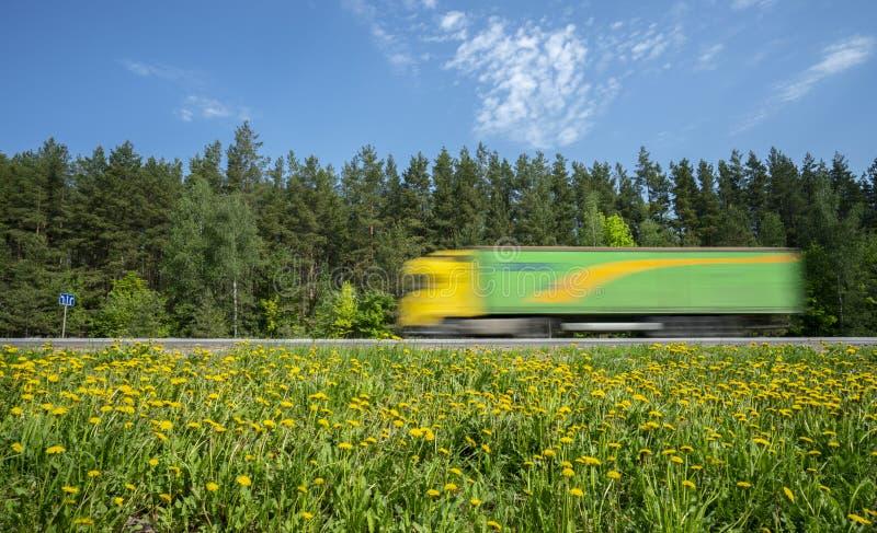 黄绿卡车沿沿森林的路冲,路旁用黄色蒲公英盖 库存图片