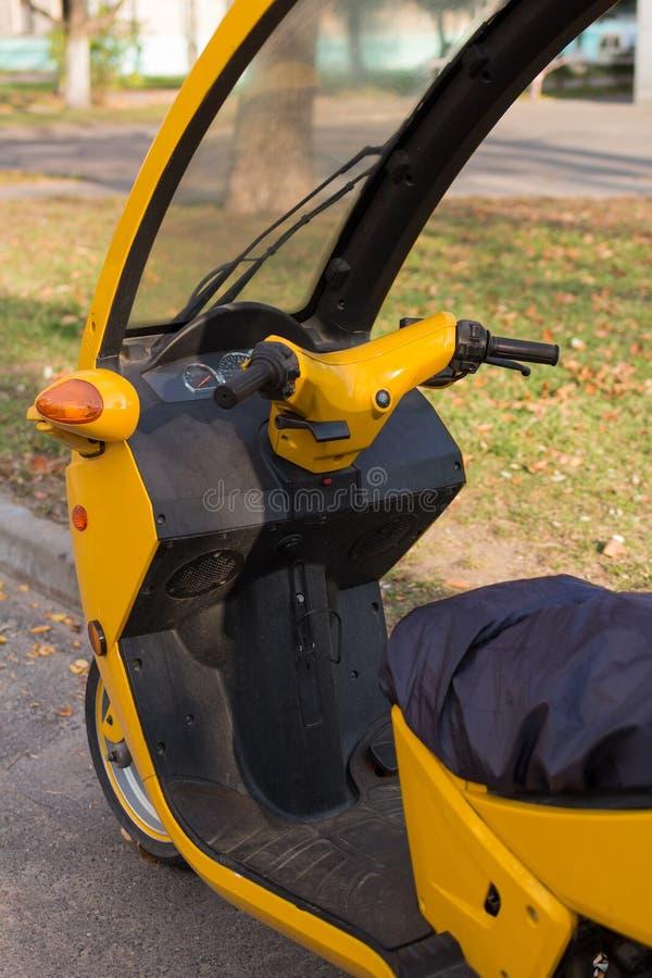 黄色三轮摩托车停车 小屋景观,周围没人 免版税库存图片