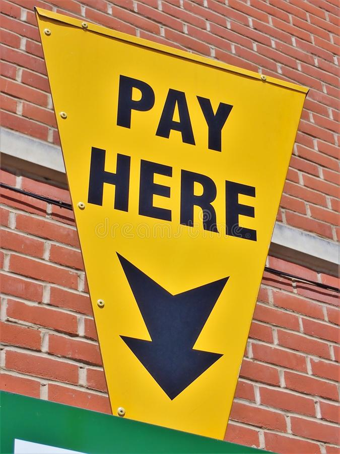 黄色与这里箭头和文本薪水的汽车停放的标志 免版税库存照片