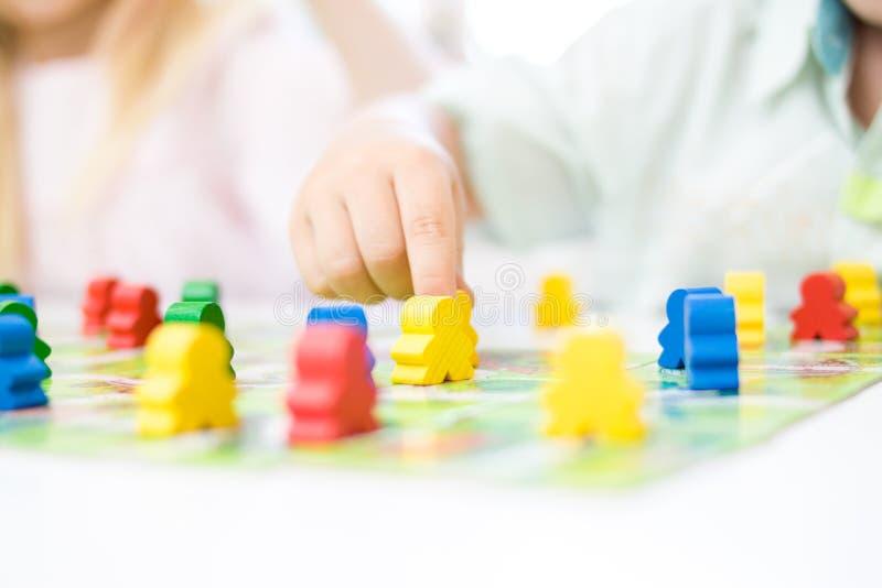 黄色人形象在手中孩子 在儿童游戏的红色,蓝色,绿色木片-棋和孩子休闲概念 库存图片