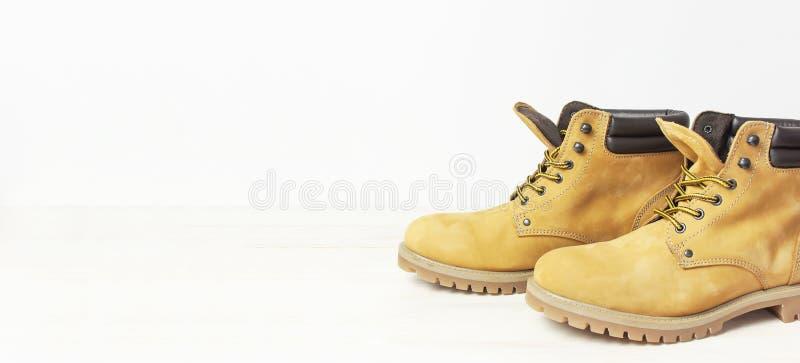 黄色人的从自然nubuck皮革的工作起动在木白色背景 时髦便鞋,青年样式 概念  库存图片