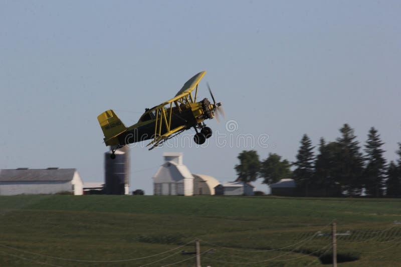 黄色作物喷粉双翼飞机 库存照片