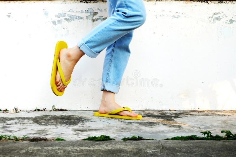 黄色凉鞋 站立在老水泥地板上的妇女佩带的触发器和蓝色牛仔裤 库存图片