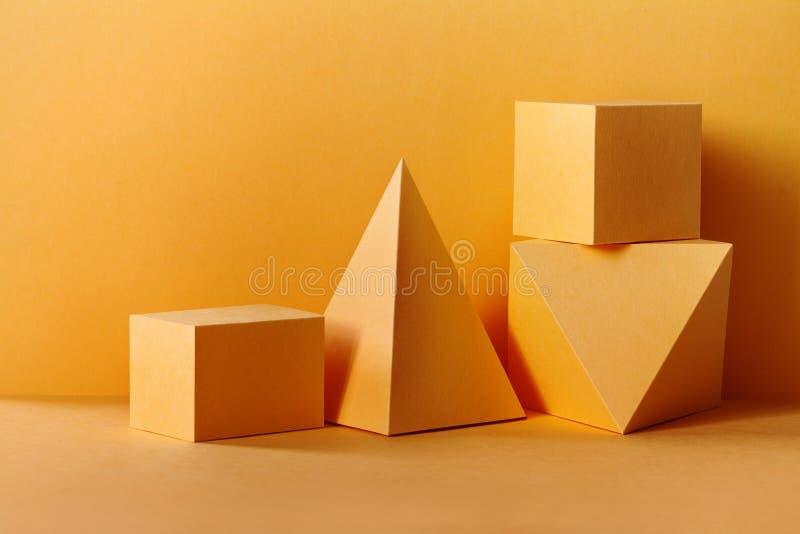 黄色几何图静物画构成 三维在黄色的棱镜金字塔长方形立方体对象 免版税库存照片