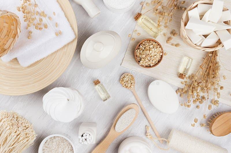 黄色化妆用品上油,燕麦粥谷物和白色奶油,在米黄木背景,顶视图的浴自然辅助部件 图库摄影
