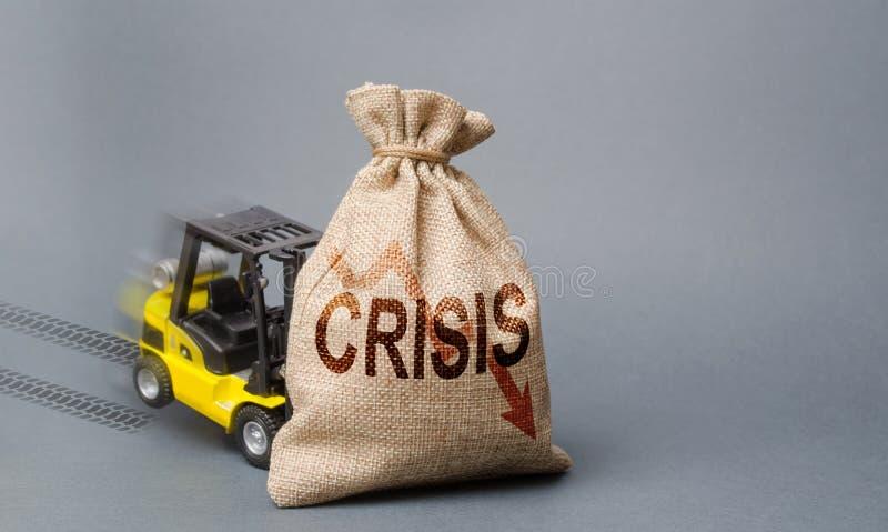 黄色叉架起货车不可能举与题字危机的袋子 经济危机、经济的停滞和后退 免版税库存照片