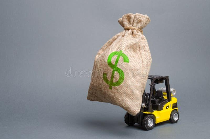 黄色叉架起货车运载一个大袋子金钱 吸引在生产的发展和现代化的投资 免版税图库摄影