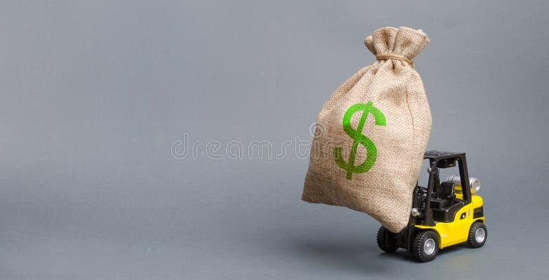 黄色叉架起货车运载一个大袋子金钱 吸引在生产的发展和现代化的投资 免版税库存图片