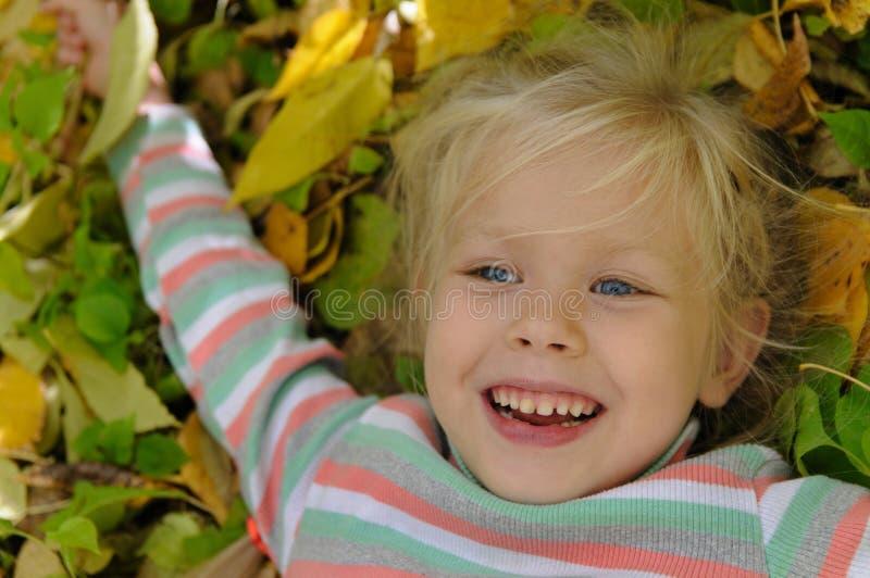 黄色叶子的女孩 图库摄影