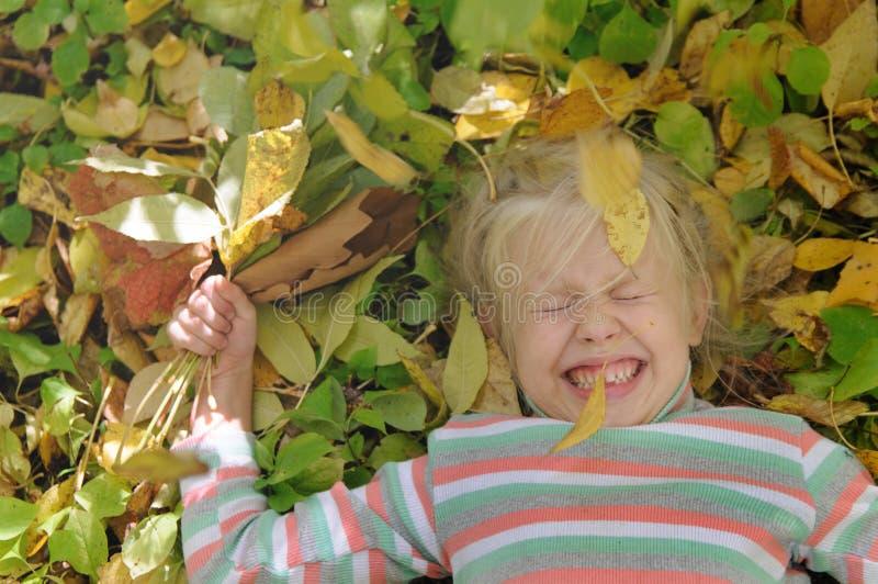 黄色叶子的女孩 库存图片