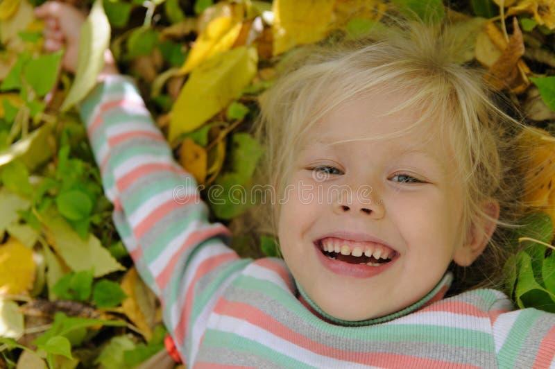 黄色叶子的女孩 免版税库存图片