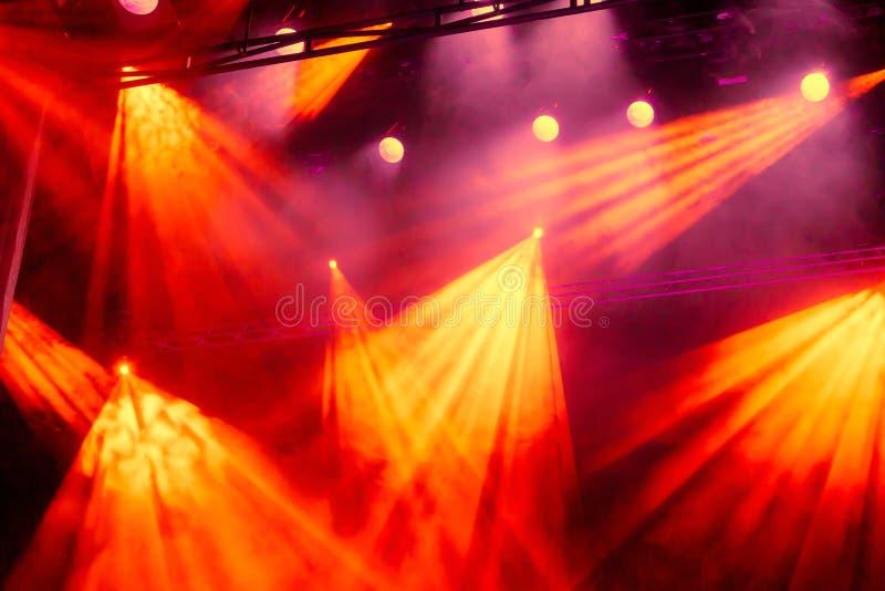 黄色和红灯从聚光灯发出光线通过烟在剧院或音乐厅 照明设备equipment.conference大厅泛光灯, 免版税图库摄影