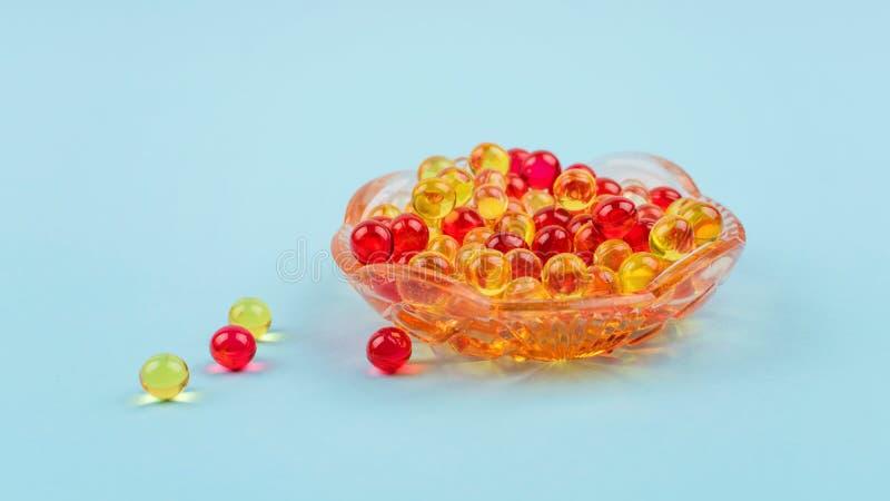 黄色和红色维生素A,E,D,Ω 3,鱼肝,鱼,晚樱草油膳食补充剂在玻璃板的胶凝体胶囊 免版税库存图片