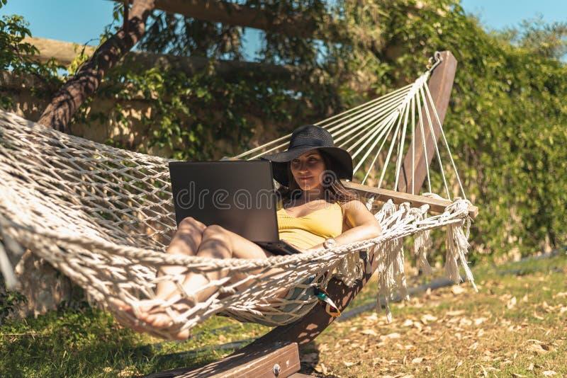 黄色在有膝上型计算机的,工作在度假,自由职业者,遥远的工作,网上收入吊床的泳装和帽子的年轻女人 库存图片