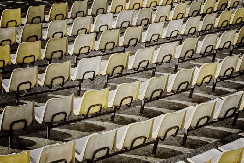 黄色塑料位子行在开放剧院背面图的 免版税库存照片