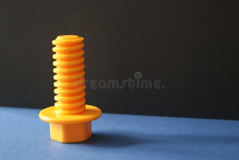 黄色塑料螺丝有黑的背景蓝色和 图库摄影