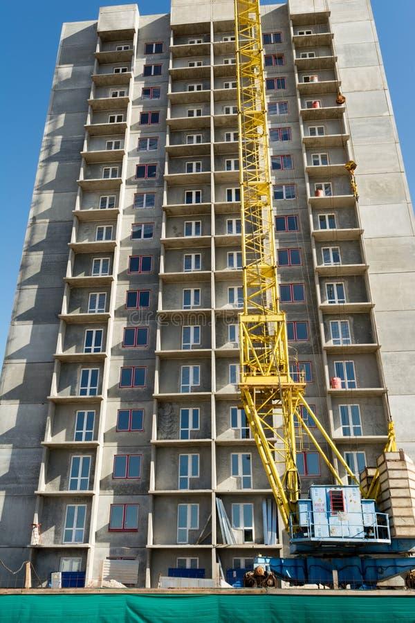黄色塔吊和一个多层的大厦的建筑反对天空蔚蓝的 库存图片