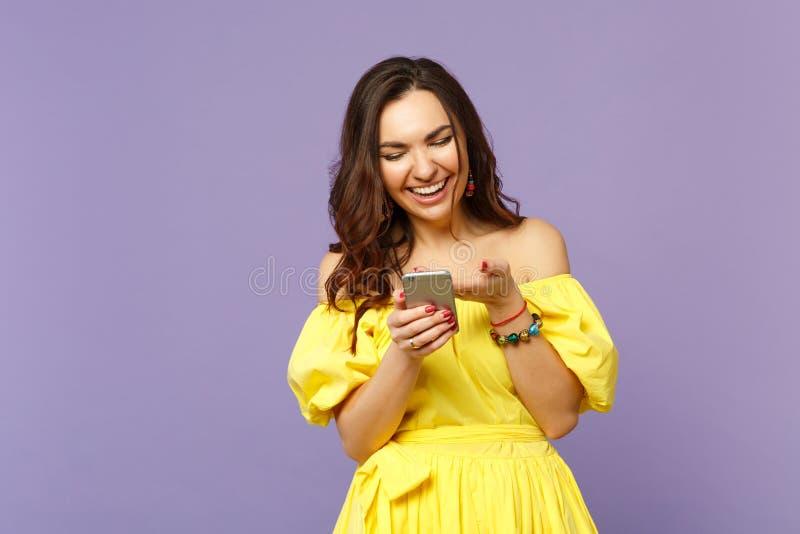 黄色夏天礼服的笑的年轻女人使用手机,在淡色紫罗兰色墙壁上隔绝的键入的sms消息 库存照片