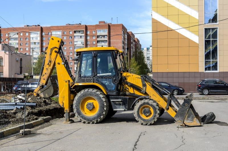 黄色大拖拉机在工作,开掘沟槽 免版税库存图片