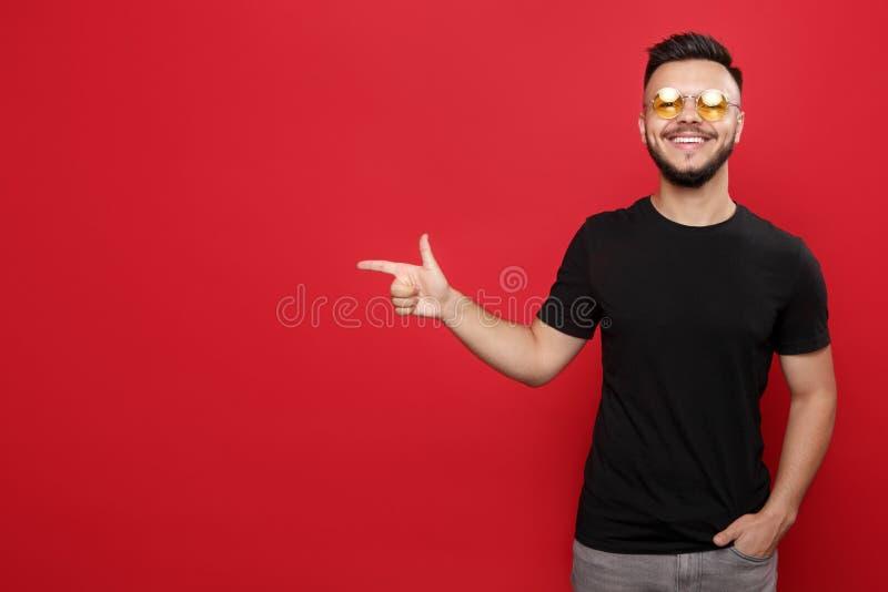 黄色太阳镜和黑T恤杉的聪慧的有胡子的人指向笑在红色背景的 库存照片