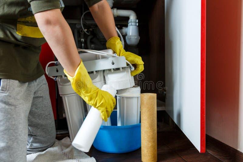 黄色家庭手套变动的水管工滤水器 安装滤水器弹药筒的安装工在厨房 免版税库存图片