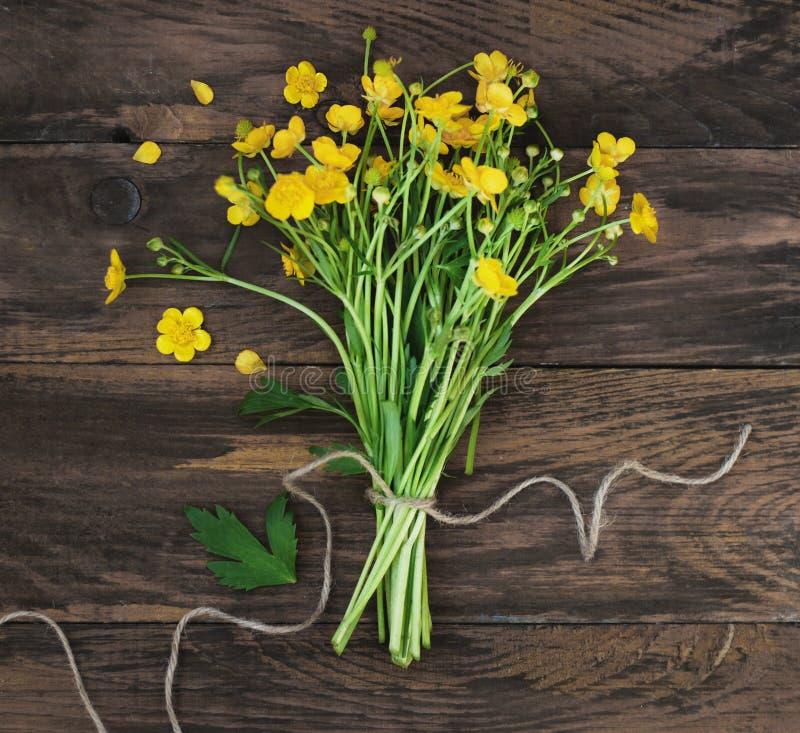 黄色小的花花束礼物春天土气木背景舱内甲板放置方形的图象 免版税图库摄影