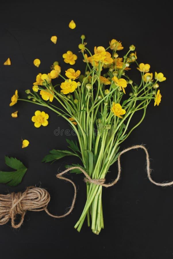 黄色小的花花束礼物春天黑色背景舱内甲板位置 免版税库存照片