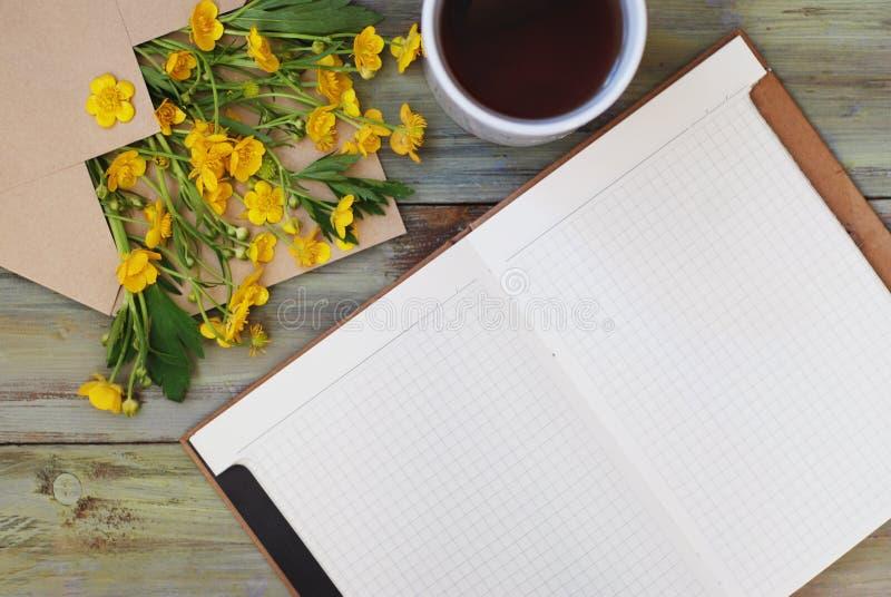 黄色小的花茶杯开放笔记本信封土气木背景舱内甲板位置 免版税库存照片