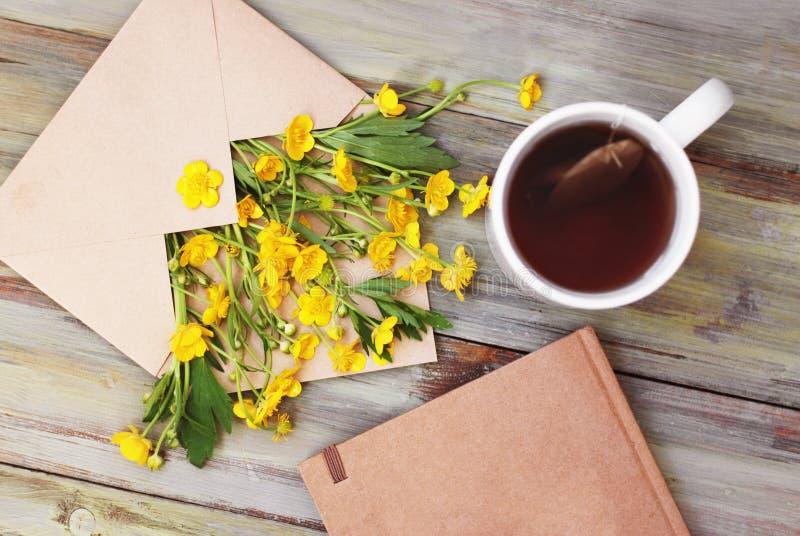黄色小的花茶杯笔记本信封土气木背景舱内甲板位置 库存图片