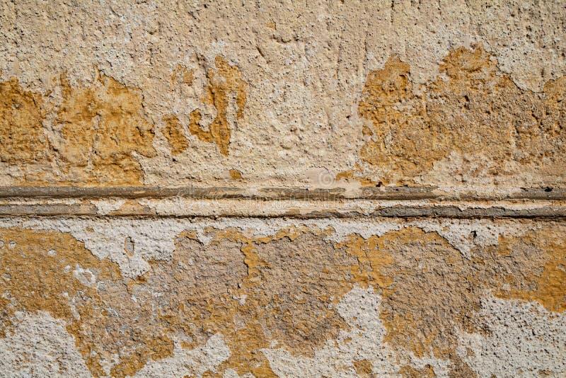 黄色崩裂了年迈的墙壁表面纹理 免版税库存图片