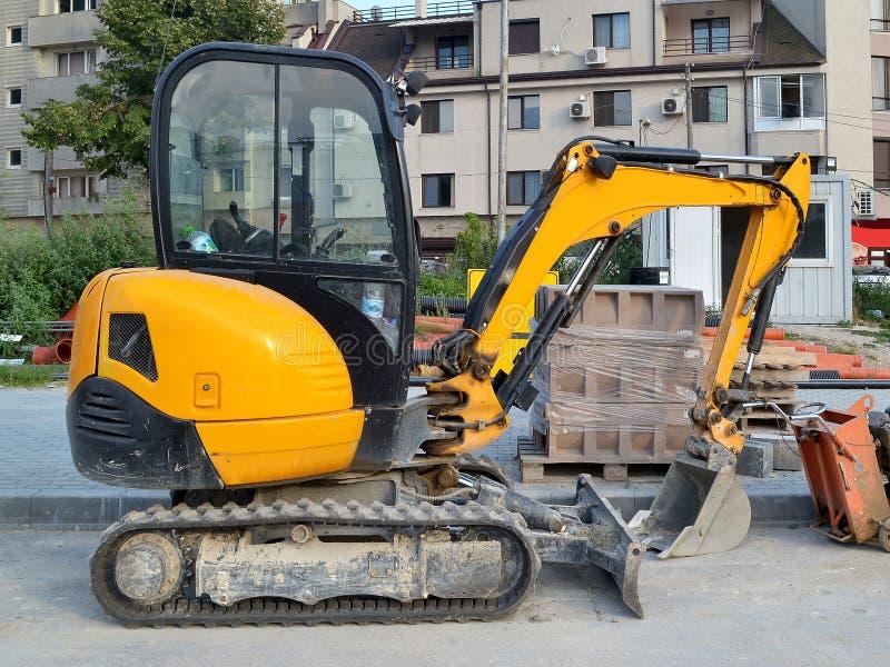 黄色微型挖掘机在小建筑工作的轨道在很难接触到地方或在狭窄的城市街道上 免版税库存照片