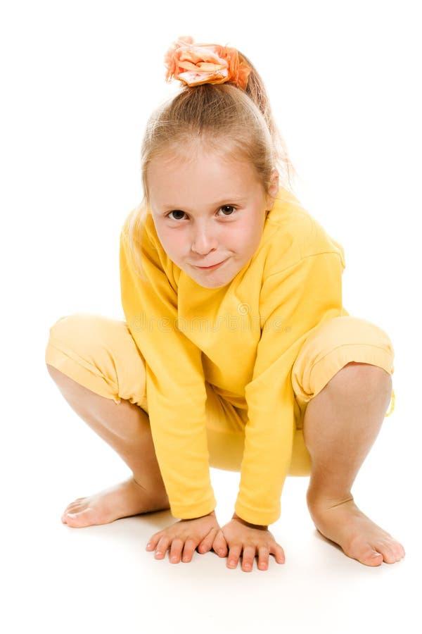 黄色微笑的逗人喜爱的女孩坐楼层 免版税库存图片