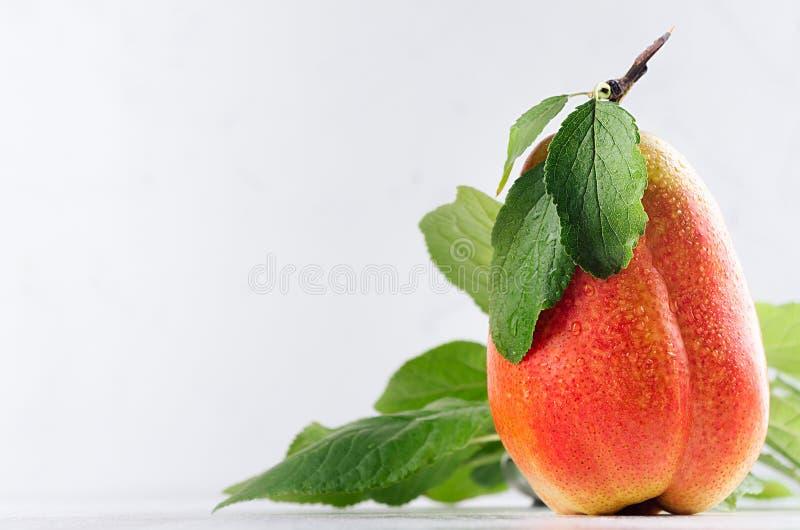 黄色成熟梨用红色边、绿色叶子和水投下在柔光白色木背景的特写镜头 健康食物背景 免版税图库摄影