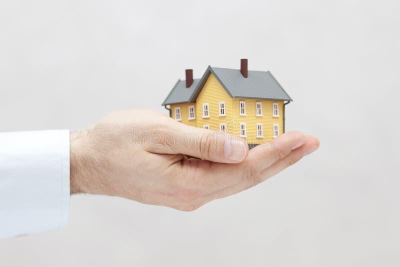 黄色房子缩样在手中 免版税图库摄影