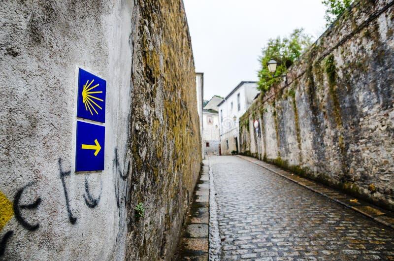 黄色扇贝壳和箭头在签署道路的墙壁上通往孔波斯特拉的圣地牙哥在加利西亚 库存照片