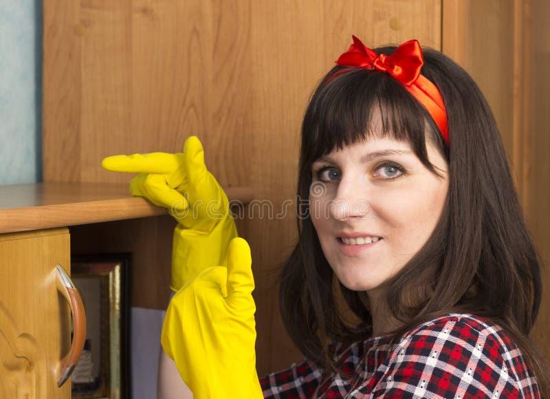 黄色手套的一个女孩抹尘土,特写镜头,妇女 免版税库存照片