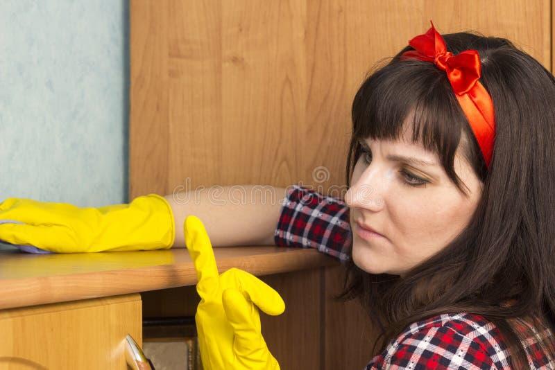 黄色手套的一个女孩抹尘土,特写镜头,黄色 免版税库存照片